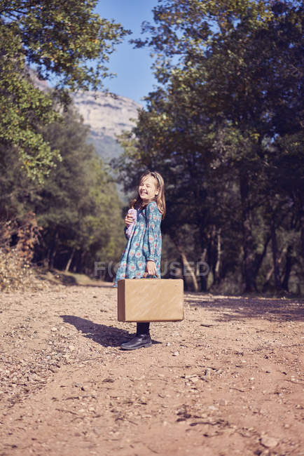 Laughing girl with a vintage suitcase — Stock Photo
