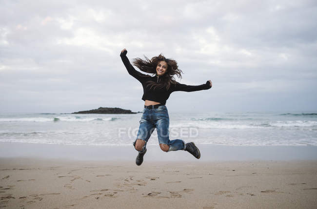 Femme heureuse sautant en l'air sur la plage — Photo de stock