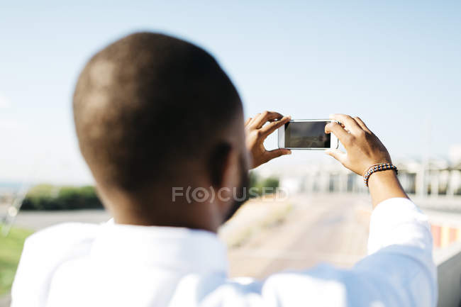 Rear view of man taking cell phone picture outdoors — Stock Photo