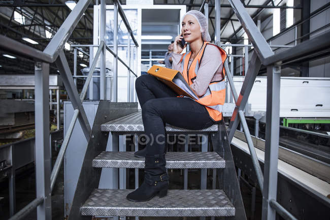 Female inspector on the phone sitting on stairs in factory — Stock Photo