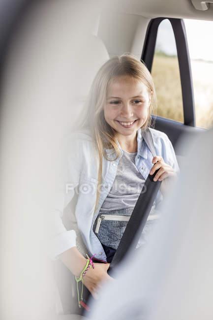 Девочка сидела в машине и крепления ремней — стоковое фото