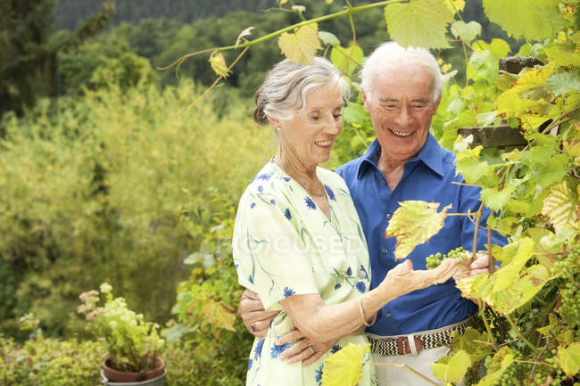 Confident senior couple standing in garden — Stock Photo