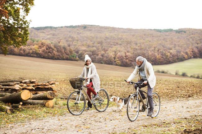 Casal sênior fazendo uma viagem de bicicleta com cão no outono — Fotografia de Stock