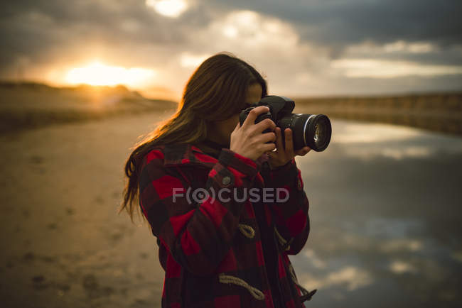 Young woman taking a photography on the beach — Stock Photo