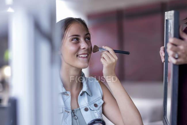 Heureuse jeune fille appliquant maquillage tandis que la mère tient miroir — Photo de stock