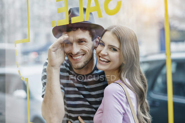 Portrait of couple looking at glass window pane — Stock Photo