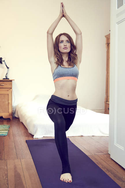 Redheaded woman doing yoga exercise at home — Stock Photo