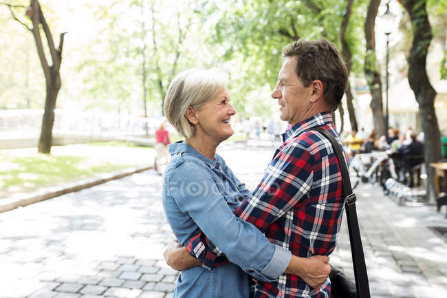Happy cute senior couple hugging each other at park — Stock Photo