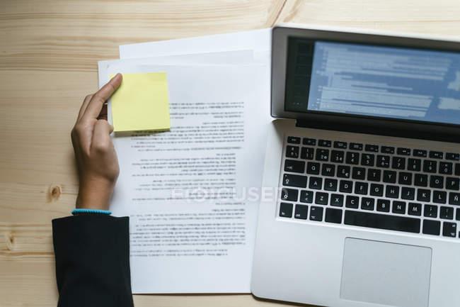 Руки положить записку на документ рядом с ноутбуком — стоковое фото