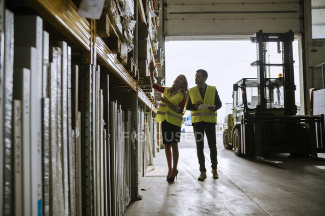 Man and woman in warehouse supervising stock — Stock Photo