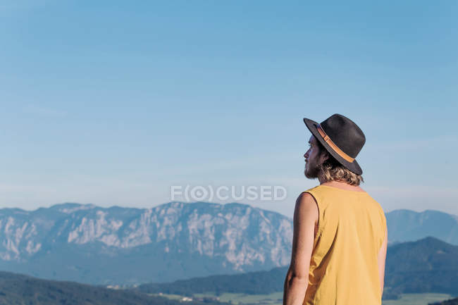 Austria, Mondsee, Mondseeberg, rear view of young man wearing a hat — Stock Photo