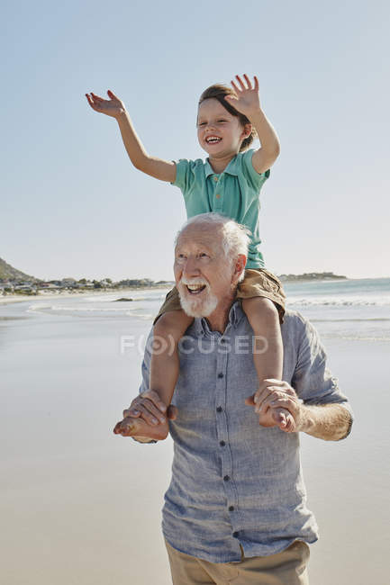 Portrait of senior man carrying grandson on shoulders — Stock Photo