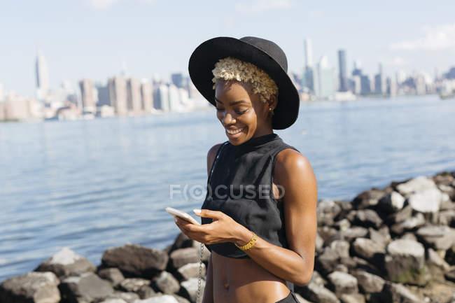 Estados Unidos, Ciudad de Nueva York, Brooklyn, joven sonriente en East River mirando el teléfono celular - foto de stock