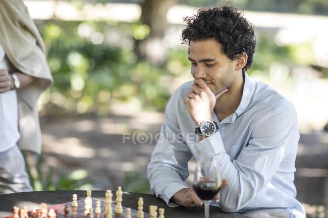 Кейптаун, Южная Африка, Мужчина сидит снаружи с шахматами, думая о своем следующем шаге — стоковое фото