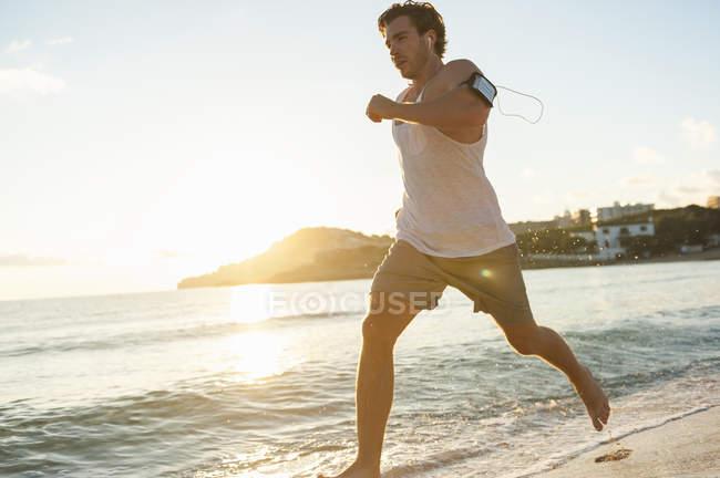 Espagne, Majorque, homme faisant du jogging sur la plage le matin — Photo de stock