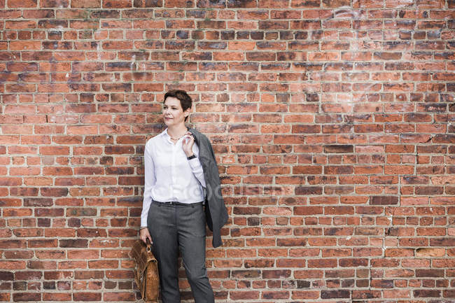 Businesswoman standing in front of brick wall — Stock Photo
