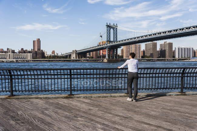 Donna d'affari guardando East River — Foto stock