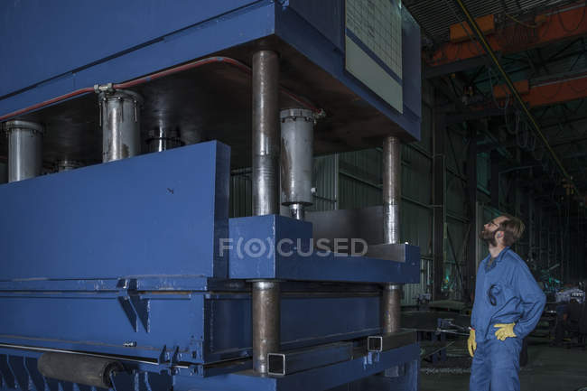 Worker inspecting machinery in factory — Stock Photo