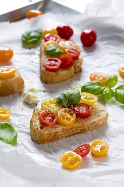 Крупним планом подання скибочки хліба з трави і нарізані помідори-чері — стокове фото