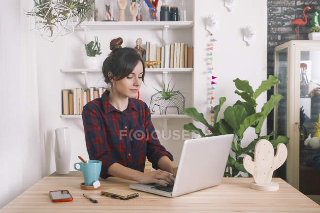 Young woman using laptop at home — Stock Photo