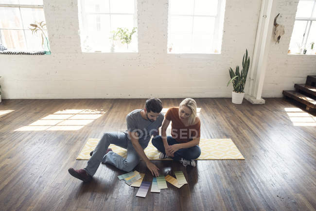 Молода пара, сидячи на килимі горищі, дивлячись на зразки кольорів — стокове фото
