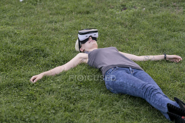 Young woman lying on a meadow wearing Virtual Reality Glasses outdoors — Stock Photo