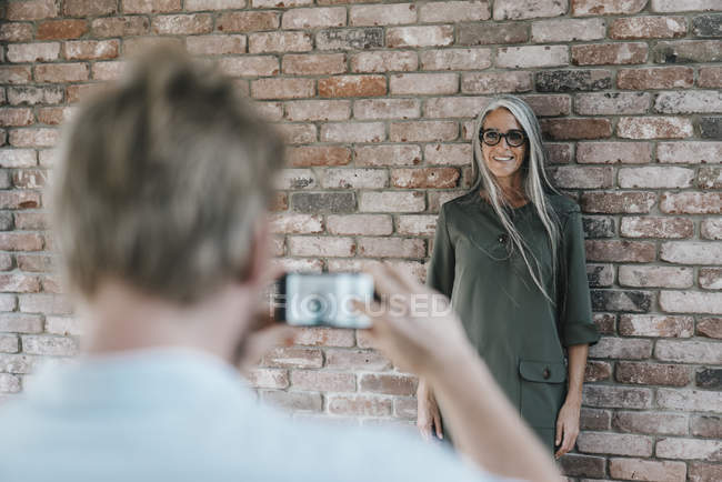Man taking picture of smiling woman with long grey hair at brick wall — Stock Photo