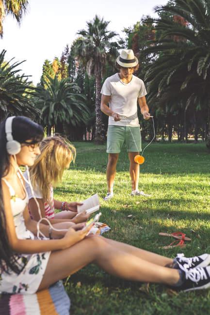 Друзів у парку відпочинку, жінок, сидячи на ковдру з книги і смартфон, людина грає з diabolo — стокове фото