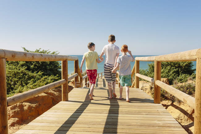 Three boys walking to the beach at summer vacation — Stock Photo