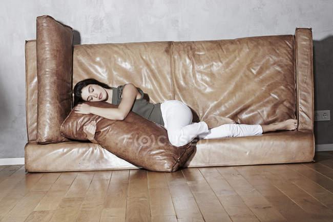 Frau entspannt sich auf umgedrehter Ledercouch — Stockfoto
