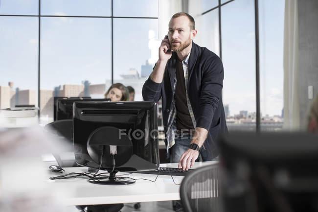 Чоловічий службовця на дзвінок на комп'ютері — стокове фото