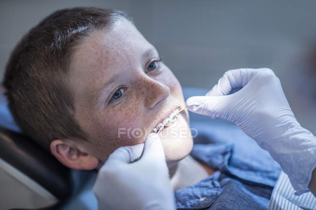 Boy with braces in dental surgery receiving dental floss treatment — Stock Photo