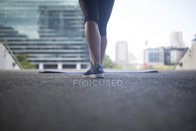 Legs of female athlete standing next to gymnastics mat in city — Stock Photo