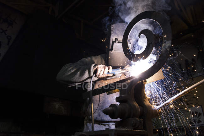 Blacksmith wearing protective workwear working in workshop — Stock Photo