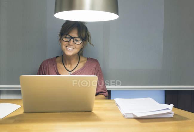 Усміхається жінка, використовуючи ноутбук на столі під ліхтарем — стокове фото