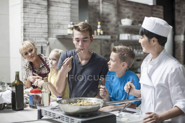 Male teen confidently tastes well cooked food with siblings in cooking class — Stock Photo