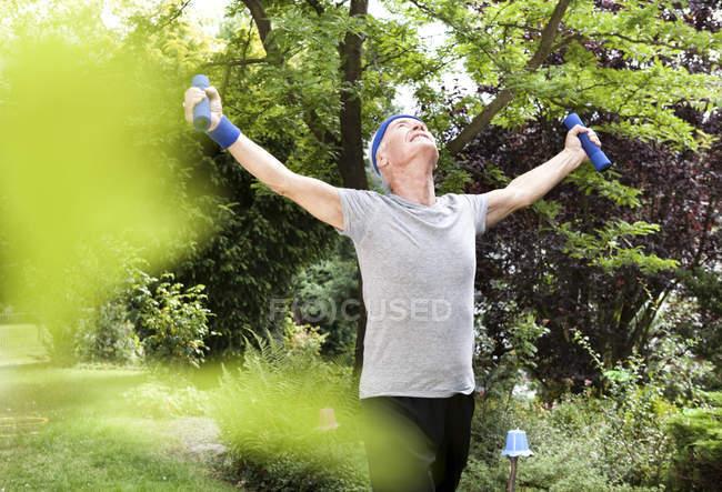 Senior man doing fitness training with dumbbells in garden — Stock Photo
