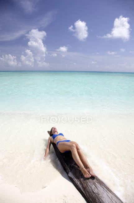 Maldivas, mujer tomando el sol en un tronco en una playa - foto de stock