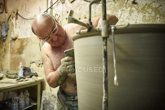 Potter in workshop working on large terracotta vase — Stock Photo