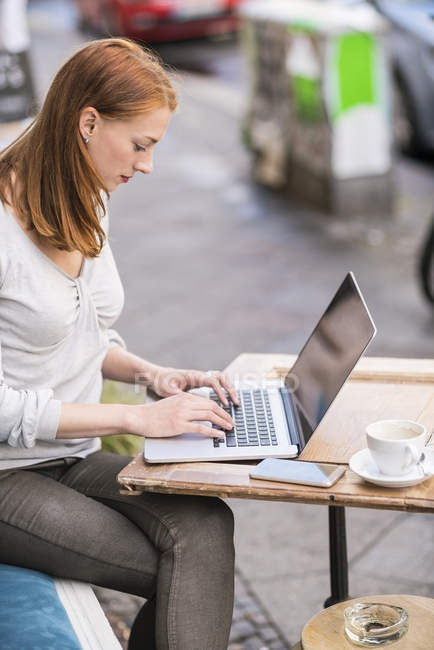 Cute redhead caucasian woman using laptop at cafe — Stock Photo