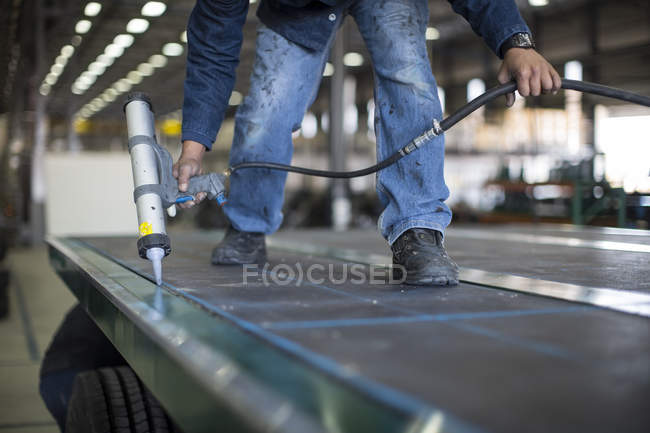 Работник с клеевой пистолет в грузовик завода — стоковое фото