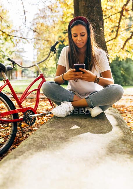 Молодая женщина отправляет сообщения со своим смартфоном в парке — стоковое фото