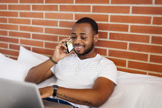Jovem sorridente usando laptop e telefone celular na cama — Fotografia de Stock