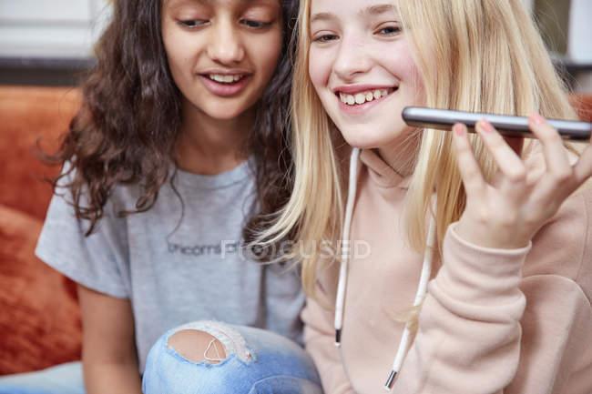 Deux filles heureuses utilisant un smartphone à la maison — Photo de stock