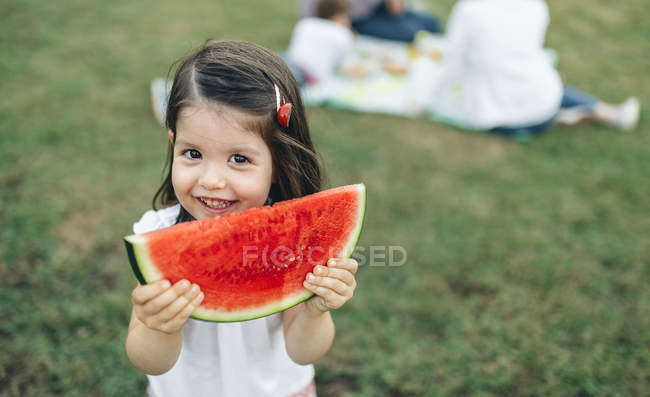 Портрет улыбающейся девушки, держащей на заднем плане ломтик арбуза со своей семьей — стоковое фото