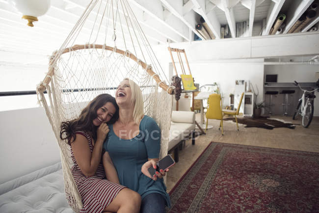 Two happy young women in hammock with cell phone — Stock Photo