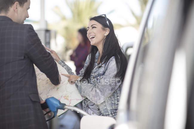 Молодая женщина, спрашивать дорогу с картой в руках на газозаправочной станции — стоковое фото