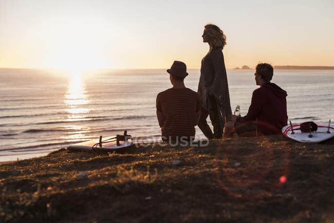 Three friends enjoying sunset on beach — Stock Photo