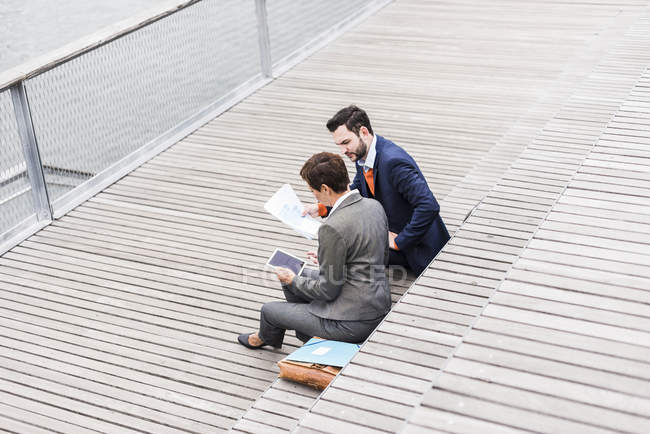 Business people meeting outdoor and holding documents and tablet — Stock Photo