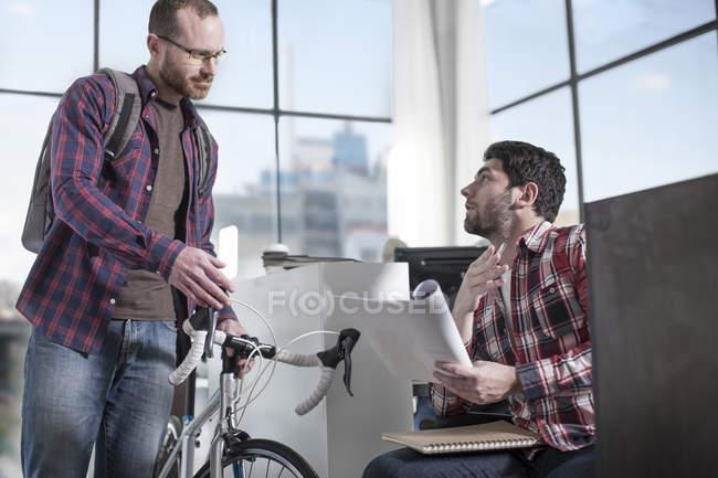 Homme décontracté avec vélo au bureau avec collègue masculin lecture magazine — Photo de stock
